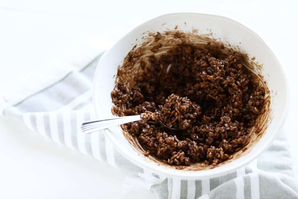 mixing rice krispie cereal and homemade chocolate sauce in white bowl on striped grey and white napkin