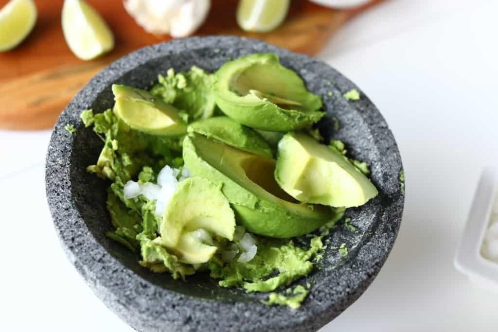 homemade guacamole - smashed avocado and onion in mocaljete