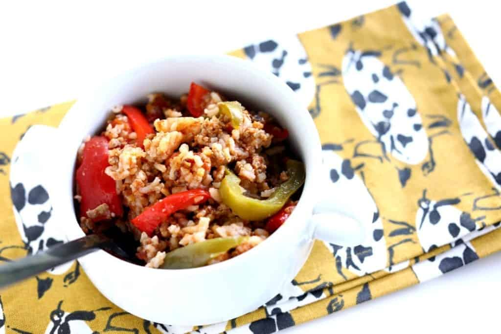 Un-stuffed turkey peppers with rice, red pepper and green pepper in a white bowl on a napkin