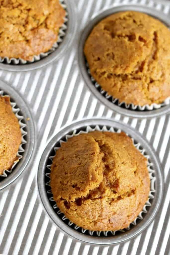 overhead shot of a fresh batch of pumpkin muffins in corregated muffin pan