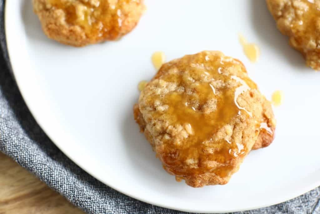 sea salt caramel apple oatmeal cookies with caramel drizzeled on top. Served on a white plate with denim napkin