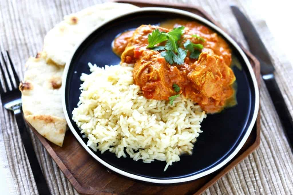 my favorite chicken tikka masala plated on a black dish with white trim, on top of a wood plate, served with naan. #chickentikkamasala #indianrecipes #indianfood #healthydinnerrecipes #chicken