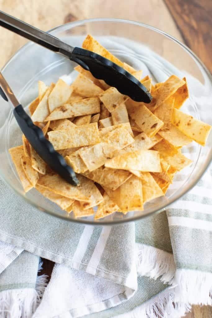 Baked & Seasoned Crispy Tortilla Strips golden brown and ready to serve with tongs in a clear glass bowl #feedfeed #f52grams #BuzzFeast #huffposttaste #ImSoMartha #thekitchn #eeeeeats #bhgfood #eattheworld #foodandwine #foodgawker #bareaders #fwx #ABMfoodie #beautifulcuisines #eatingfortheinsta #foodwinewomen #yahoofood #foodblogfeed #foodblogeats #theeverygirl #thatsdarling #dailyfoodfeed #foodphotography #foodblogeats #tortillastrips #snack #healthysnacks #bakedchips #bingeworthybites
