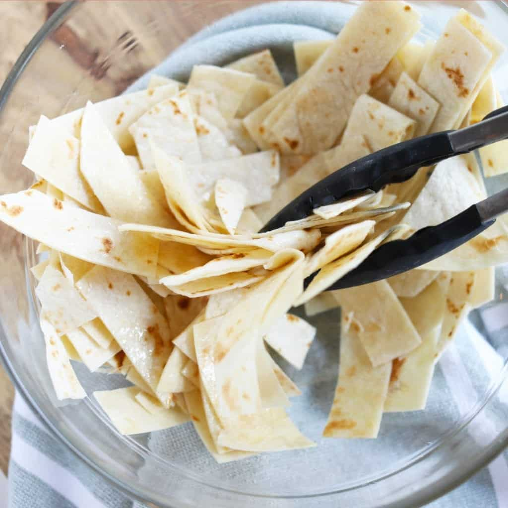 Tossing tortilla strips in a clear glass bowl with tongs after lightly coating them with oil #feedfeed #f52grams #BuzzFeast #huffposttaste #ImSoMartha #thekitchn #eeeeeats #bhgfood #eattheworld #foodandwine #foodgawker #bareaders #fwx #ABMfoodie #beautifulcuisines #eatingfortheinsta #foodwinewomen #yahoofood #foodblogfeed #foodblogeats #theeverygirl #thatsdarling #dailyfoodfeed #foodphotography #foodblogeats #tortillastrips #snack #healthysnacks #bakedchips #bingeworthybites
