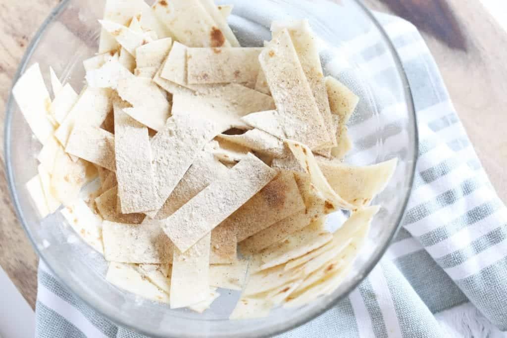 tortilla strips in a clear glass bowl seasoned with seasoned salt and garlic powder before seasonings have been mixed and evenly coated #feedfeed #f52grams #BuzzFeast #huffposttaste #ImSoMartha #thekitchn #eeeeeats #bhgfood #eattheworld #foodandwine #foodgawker #bareaders #fwx #ABMfoodie #beautifulcuisines #eatingfortheinsta #foodwinewomen #yahoofood #foodblogfeed #foodblogeats #theeverygirl #thatsdarling #dailyfoodfeed #foodphotography #foodblogeats #tortillastrips #snack #healthysnacks #bakedchips #bingeworthybites