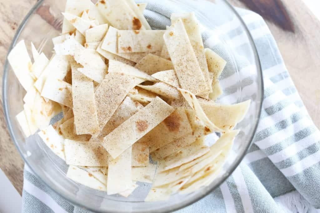 tortilla strips in a clear glass bowl seasoned with seasoned salt before seasoning has been mixed and evenly coated #feedfeed #f52grams #BuzzFeast #huffposttaste #ImSoMartha #thekitchn #eeeeeats #bhgfood #eattheworld #foodandwine #foodgawker #bareaders #fwx #ABMfoodie #beautifulcuisines #eatingfortheinsta #foodwinewomen #yahoofood #foodblogfeed #foodblogeats #theeverygirl #thatsdarling #dailyfoodfeed #foodphotography #foodblogeats #tortillastrips #snack #healthysnacks #bakedchips #bingeworthybites