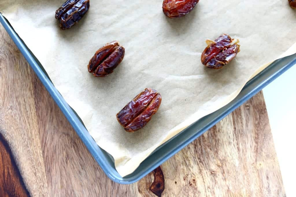 Overhead picture of prepared pitted dates sliced down the middle on pan with parchment paper #bingeworthybites #baconwrappeddateswithcheese #baconwrappeddates #thanksgivingappetizers #appetizers #partyappetizers