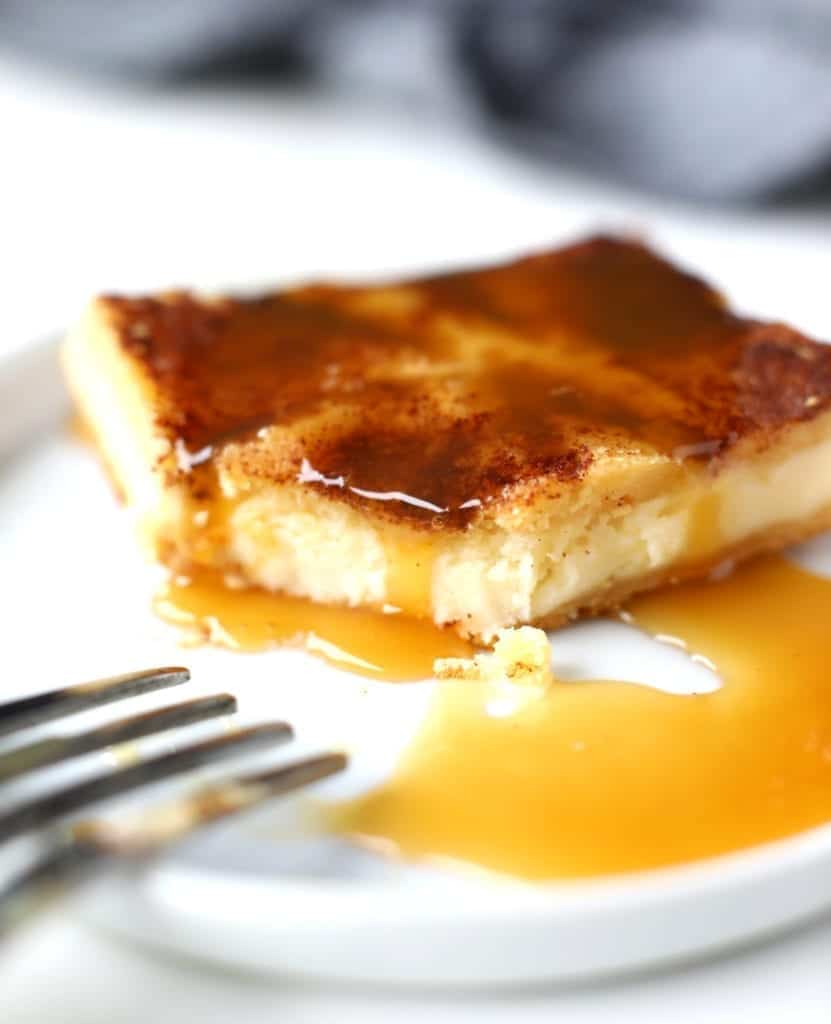 Up close picture of Sopapilla [Churro} Cheesecake Bars with caramel drizzled on top served on a white plate. #thanksgivingdessert #cheesecakebars #cheesecake #sopapillacheesecakebars #sopapillacheesecake #dessert #easydessert #bingeworthybites
