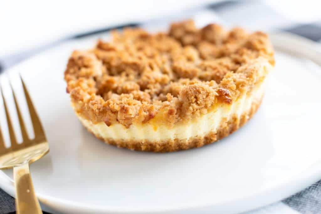 Up close picture of mini caramel apple cheesecakes with streusel on top (caramel has not been added) Served on white plate with gold fork. #dessert #streusel #cheesecake #caramelapplecheesecake #dessert #streusel #pie #minipies #applepie #baking #easyrecipes #bingeworthybites