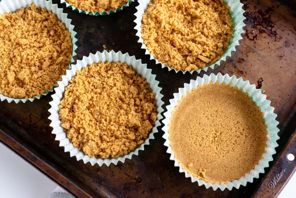 Up close picture of graham cracker crust for mini caramel apple cheesecakes with streusel on top #dessert #streusel #cheesecake #caramelapplecheesecake #dessert #streusel #pie #minipies #applepie #baking #easyrecipes #bingeworthybites