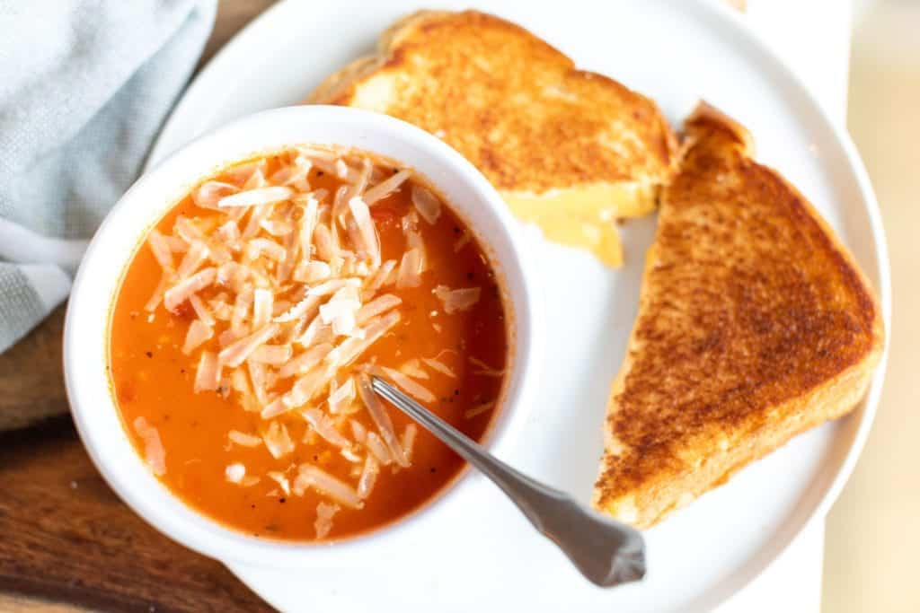 overhead picture of THE BEST homemade tomato soup with parmesan cheese on top & grilled cheese sandwich sliced in half served in a white bowl and on a white plate #feedfeed #f52grams #BuzzFeast #SWEEEEETS #huffposttaste #ImSoMartha #surlatable #mywilliamssonoma #thekitchn #eeeeeats #bhgfood #eattheworld #bakersofinstagram #foodandwine #foodgawker #bareaders #fwx #ABMfoodie #beautifulcuisines #eatingfortheinsta #foodwinewomen #yahoofood #foodblogfeed #foodblogeats #theeverygirl #thatsdarling #dailyfoodfeed #foodphotography #foodblogeats