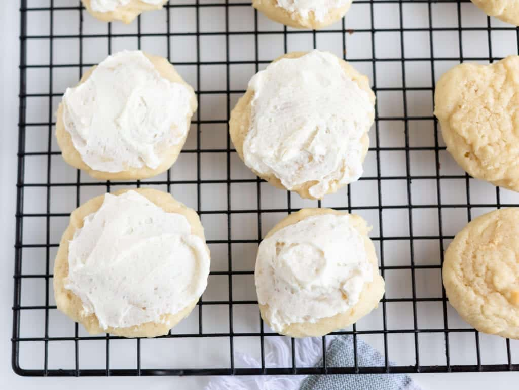 soft sugar cookie cooled and frosted on cooling rack. Half of cookies in photo are frosted with white vanilla frosting 9 cookies in picture #sugarcookies #lofthousecookiedupe #softsugarcookies #frostedsugarcookie #homemadefrosting #dessert #baking #easyrecipes #bingeworthybites #homemadecookierecipes #bestcookierecipes #softestsugarcookies