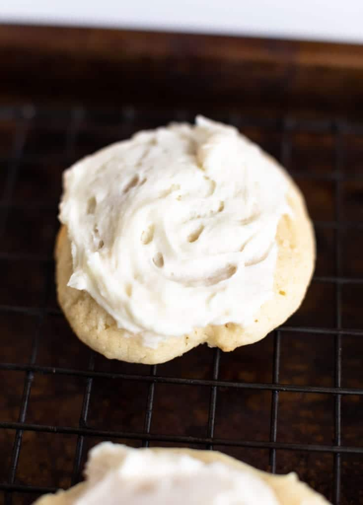 up close picture of soft frosted sugar cookie with white vanilla cream frosting on cooling rack #sugarcookies #lofthousecookiedupe #softsugarcookies #frostedsugarcookie #homemadefrosting #dessert #baking #easyrecipes #bingeworthybites #homemadecookierecipes #bestcookierecipes #softestsugarcookies