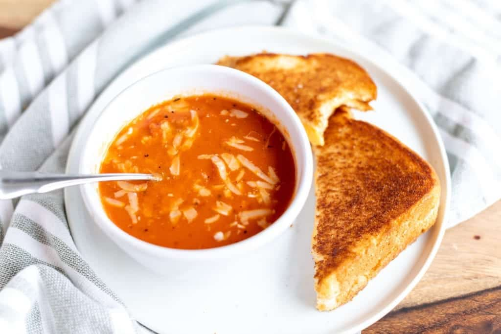 overhead picture of THE BEST homemade tomato soup with parmesan cheese on top & grilled cheese cut in half with bite missing - served in a white bowl on a white plate #feedfeed #f52grams #BuzzFeast #SWEEEEETS #huffposttaste #ImSoMartha #surlatable #mywilliamssonoma #thekitchn #eeeeeats #bhgfood #eattheworld #bakersofinstagram #foodandwine #foodgawker #bareaders #fwx #ABMfoodie #beautifulcuisines #eatingfortheinsta #foodwinewomen #yahoofood #foodblogfeed #foodblogeats #theeverygirl #thatsdarling #dailyfoodfeed #foodphotography #foodblogeats