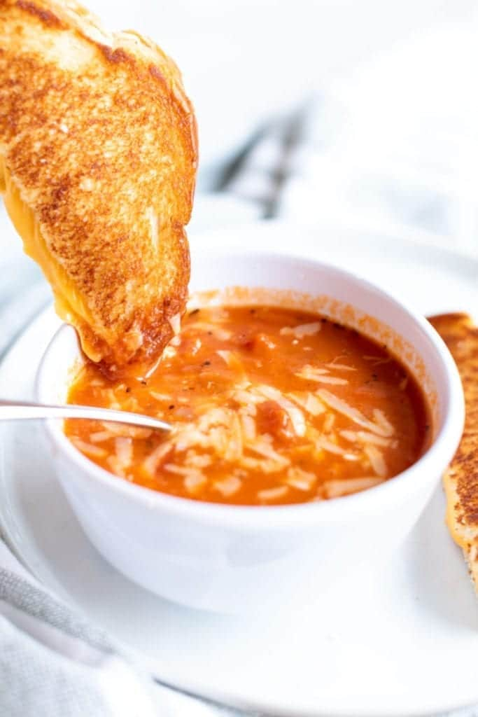 Up close picture of THE BEST homemade tomato soup with parmesan cheese on top & grilled cheese recipe served in a white bowl on a white plate #feedfeed #f52grams #BuzzFeast #SWEEEEETS #huffposttaste #ImSoMartha #surlatable #mywilliamssonoma #thekitchn #eeeeeats #bhgfood #eattheworld #bakersofinstagram #foodandwine #foodgawker #bareaders #fwx #ABMfoodie #beautifulcuisines #eatingfortheinsta #foodwinewomen #yahoofood #foodblogfeed #foodblogeats #theeverygirl #thatsdarling #dailyfoodfeed #foodphotography #foodblogeats