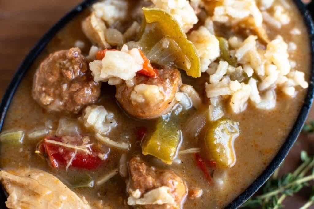 Close up Leftover Turkey Andouille Gumbo served in a cast iron bowl with spoon on a wooden plate #feedfeed #f52grams #huffposttaste #ImSoMartha #thekitchn #eeeeeats #bhgfood #foodandwine #foodgawker #bareaders #fwx #beautifulcuisines #foodblogfeed #dailyfoodfeed #ktchn #comfortfoods #BuzzFeast #bingeworthybites #soup #stew #gumbo #turkeygumbo #thanksgivingleftovers #leftoverchicken #leftoverrecipes #lecreuset #leftovers #leftoverturkey #nomnomnom #onthetable
