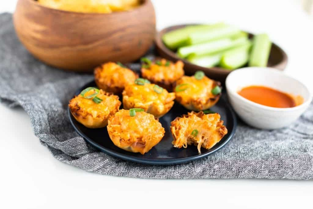 Seven Buffalo Chicken Cups on a navy blue plate and denim napkin with Frank's RedHot Dipping sauce, and celery sticks and tortilla chips on the side. Focal point is of Buffalo Chicken Cups topped with chopped green onions one of the buffalo chicken cups has a bite taken out of it #bingeworthybites #gameday #appetizers #partyfood #fingerfood #spicy #chicken #phyllocups #frankshotsauce #franksredhotsauce #hotsauce #dip #superbowlfood #superbowl #superbowlparty
