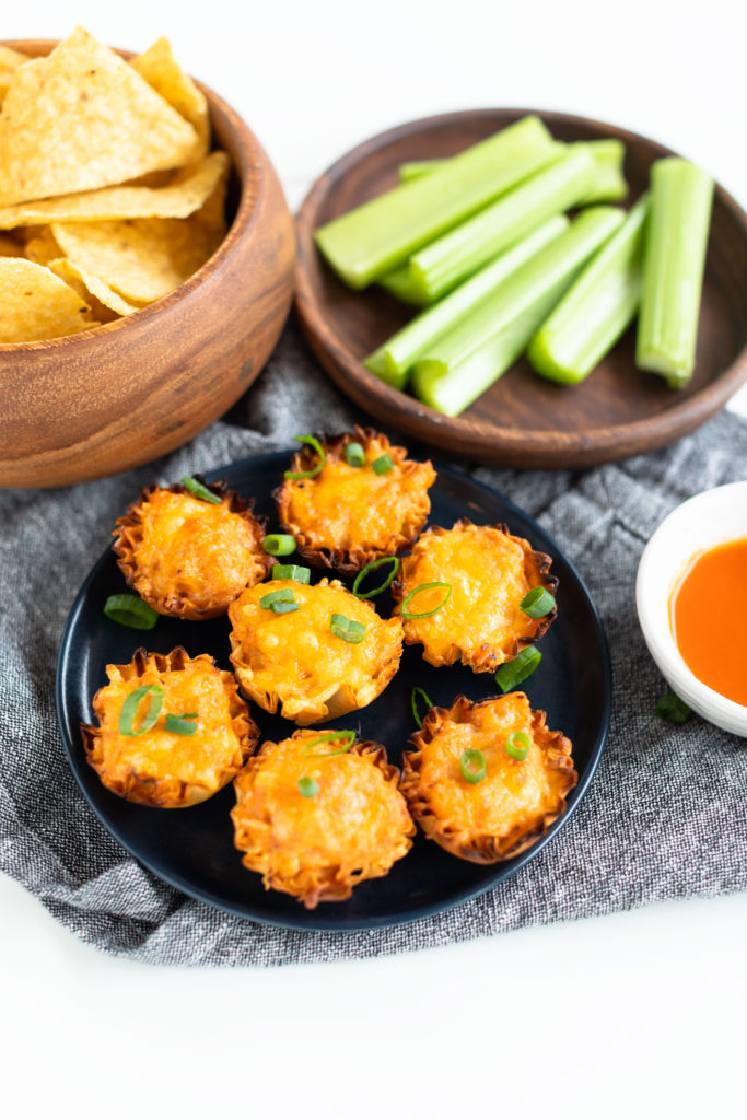 Seven Buffalo Chicken Cups on a navy blue plate and denim napkin with Frank's RedHot Dipping sauce, and celery sticks and tortilla chips on the side. Focal point is of Buffalo Chicken Cups topped with chopped green onions #bingeworthybites #gameday #appetizers #partyfood #fingerfood #spicy #chicken #phyllocups #frankshotsauce #franksredhotsauce #hotsauce #dip #superbowlfood #superbowl #superbowlparty