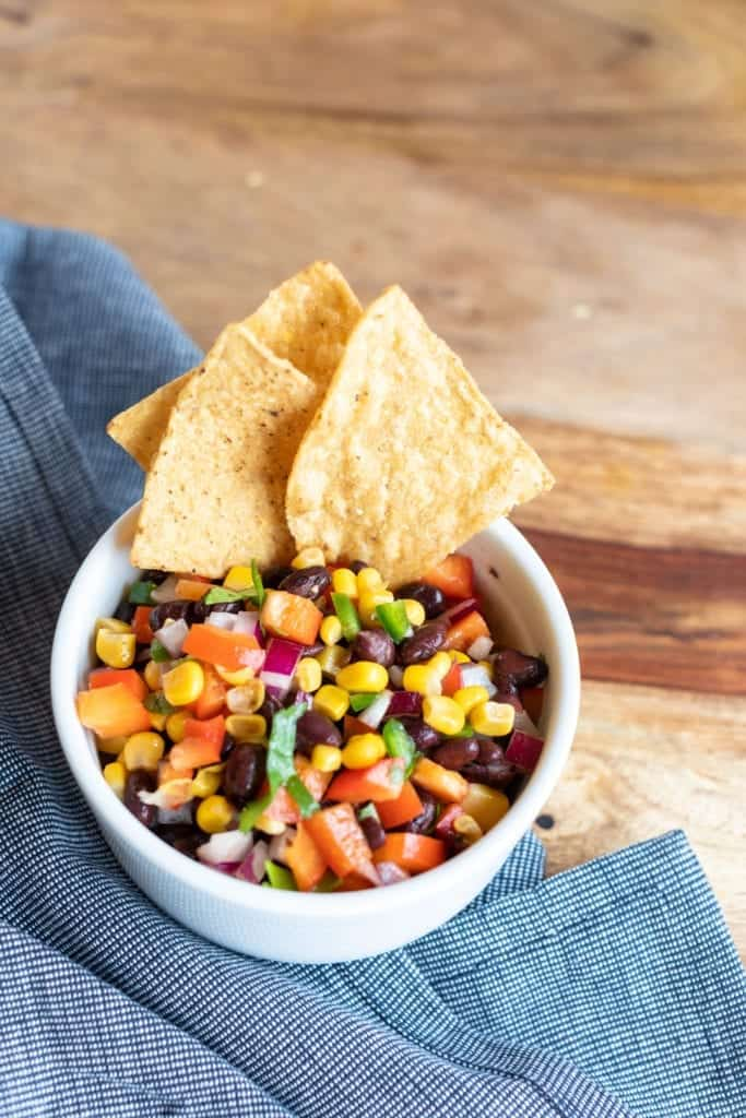 Cowboy caviar/Texas Caviar dip in white bowl with tortilla chips on top with a denim napkin #bingeworthybites #newyearnewdiet #cowboycaviar #texascaviar #turkey #easyrecipes #turkeywrap #turkeyrollup #foodphotography #williamsonoma #chipsanddip #dip