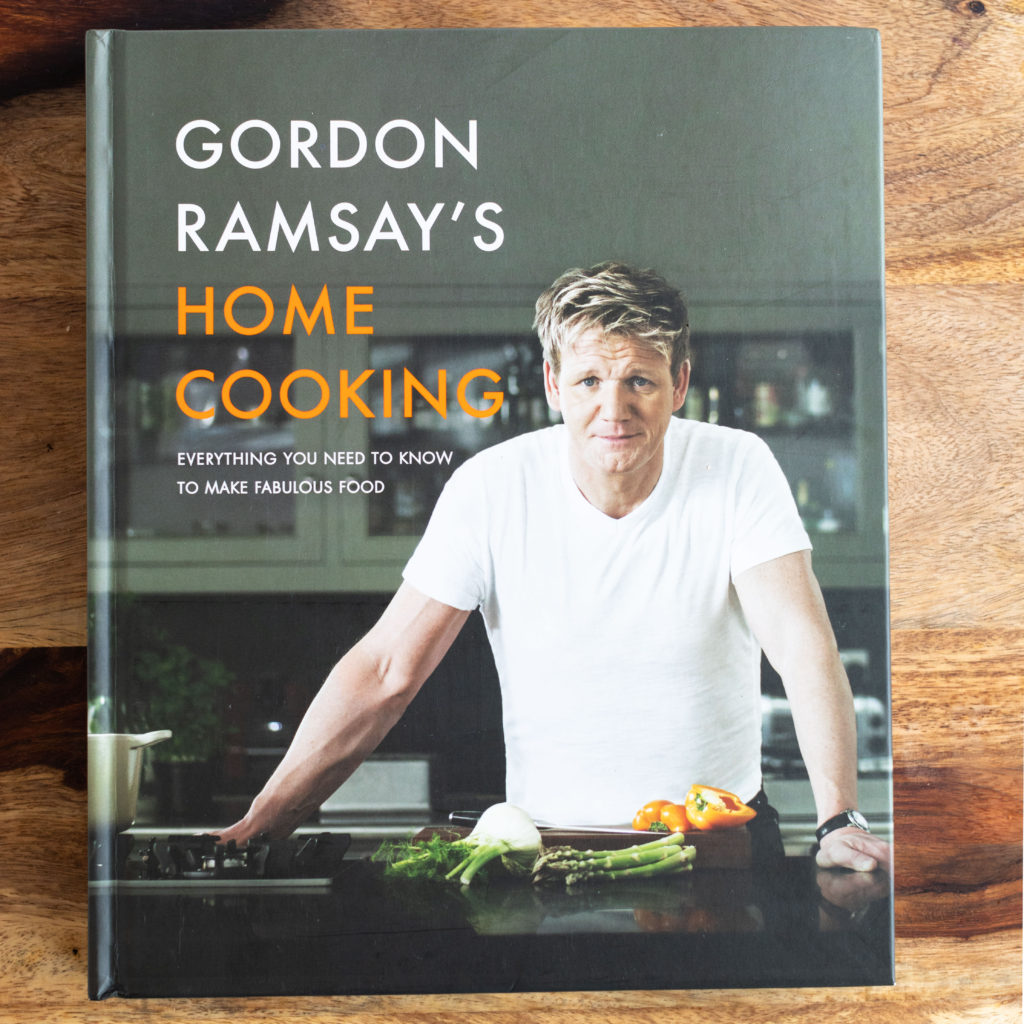 Gordon Ramsay's Home Cooking Book Review of Pork Chops with Peppers - photo of book cover on wood cutting board #porkchops #homecooking #recipe #dinner #easyrecipes #gordonramsayrecipes #gordonramsayporkchop #porkchop #peppers #sweetandsourpeppers #gordonramsay #cookbookreview #bestcookbooks