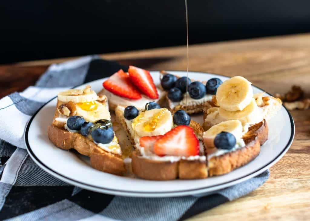 Honey being drizzled on ricotta & fruit on warm toast made with banana, blueberry, strawberry, walnut, ricotta cheese spread on toast. Served on white plate with plaid napkin #ricottatoast #ricottafruittoast #healthybreakfast #weightwatchers #weightwatchersnackrecipes #weightwatchersfreestyle #WW #toast #healthysnacks #snacks #cheese #freshfruit #fruit #bingeworthybites