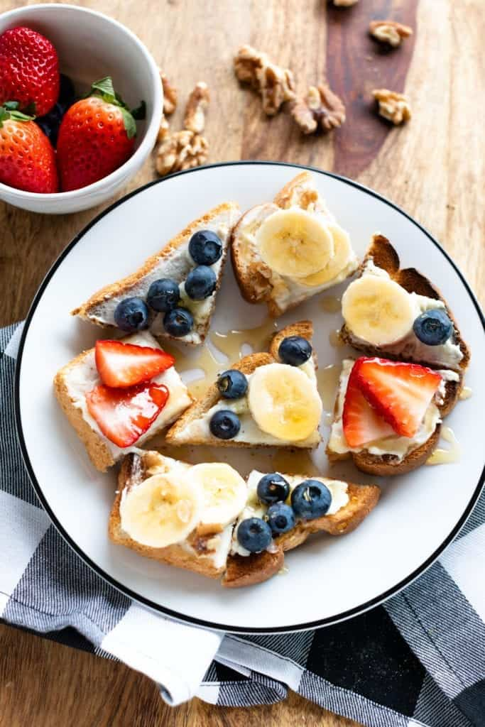 Overhead shot of Honey drizzled ricotta & fruit on toast made with banana, blueberry, strawberry, walnut, ricotta cheese spread on toast. Served on white plate with plaid napkin #ricottatoast #ricottafruittoast #healthybreakfast #weightwatchers #weightwatchersnackrecipes #weightwatchersfreestyle #WW #toast #healthysnacks #snacks #cheese #freshfruit #fruit #bingeworthybites