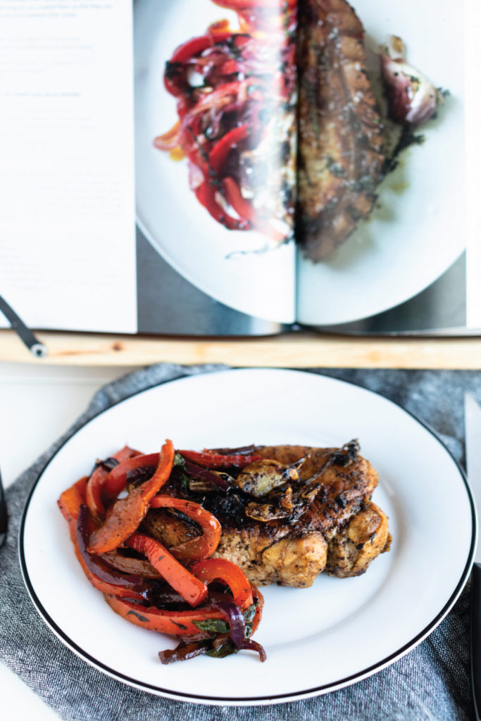 Gordon Ramsay's Pork Chops with Peppers: beautifully sautéed pork chop and sweet and sour peppers served on the side. Plated on a white dish with black rim and denim napkin with cookbook in backdrop for comparison #porkchops #homecooking #recipe #dinner #easyrecipes #gordonramsayrecipes #gordonramsayporkchop #porkchop #peppers #sweetandsourpeppers #gordonramsay #cookbookreview #bestcookbooks