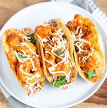 3 Spicy Shrimp Tacos with Cilantro Garlic & Refried Beans and Monterery jackon top on taco rack ready to serve #WW #tacos #tacotuesday #spicyshrimptacos #easyrecipes #healthyrecipes #besttacorecipes #shrimprecipes #refriedbeans #spicy #dinner #maincourse #appetizer #bingeworthybites
