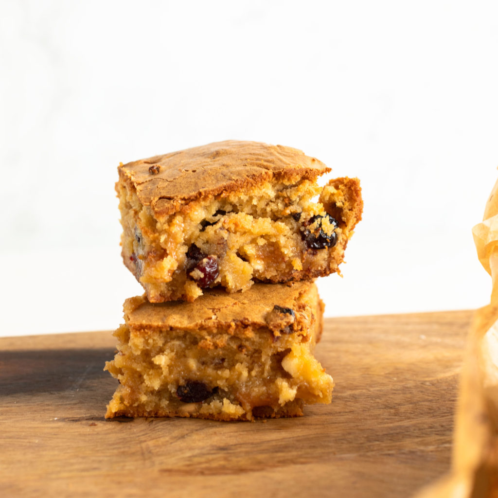 2 White Chocolate Cranberry Blondies with Caramels ready to eat stacked on on top of the other served on a wood cutting board #bingeworthybites #dessert #cranberry #blondies #whitechocolate #valentinesdaydessert #recipe