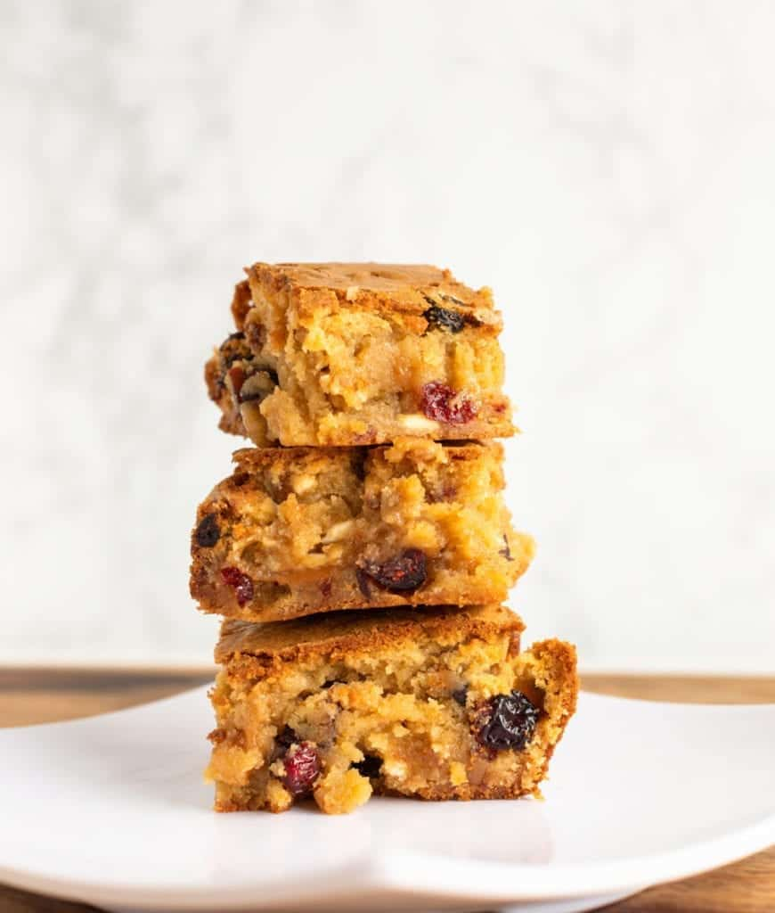Three stacked White Chocolate Cranberry Blondies with Caramel on a white plate #bingeworthybites #dessert #cranberry #blondies #whitechocolate #valentinesdaydessert #recipe