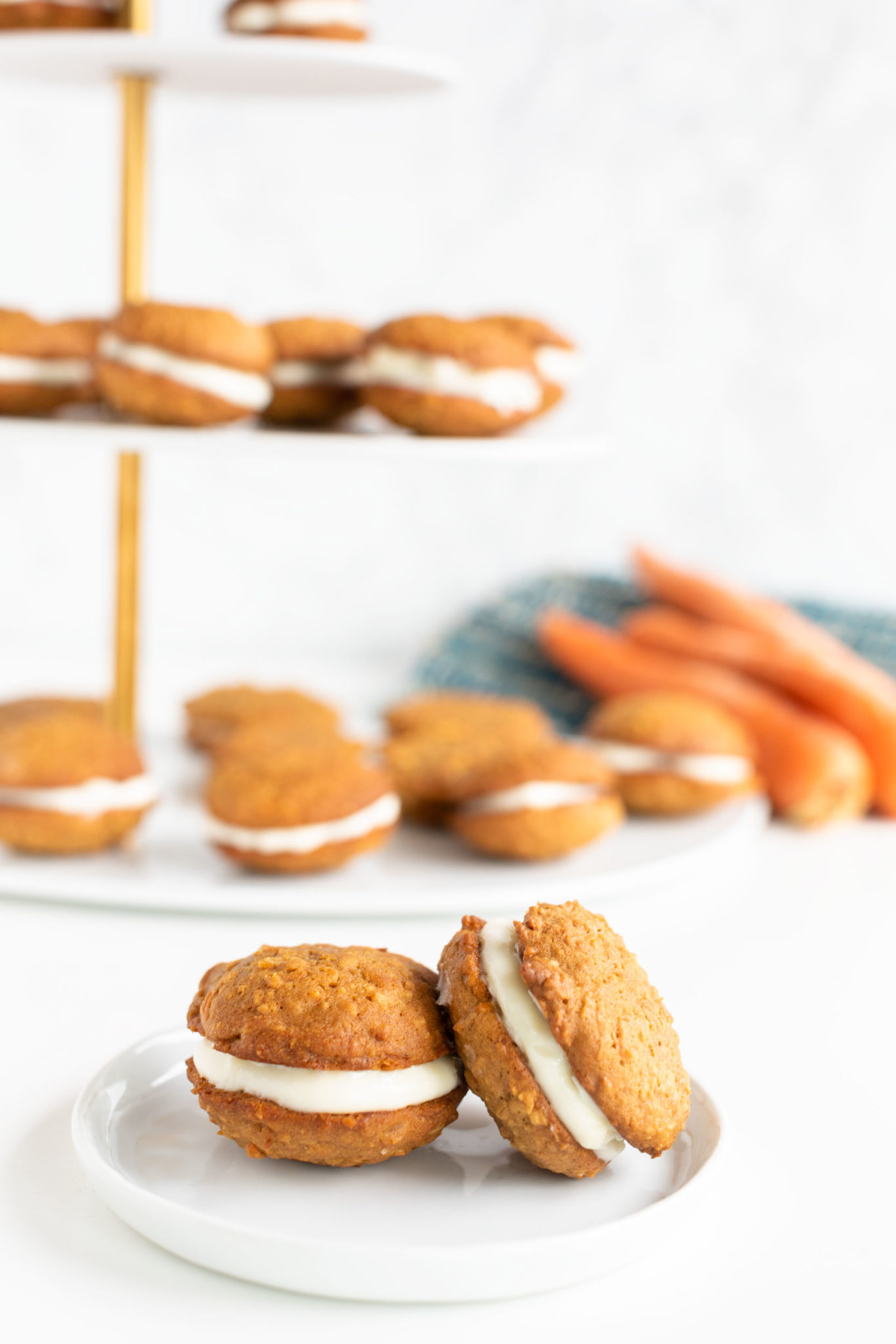 two cookie sandwiches on white plate with tiered display filled with cookie sandwiches in the background
