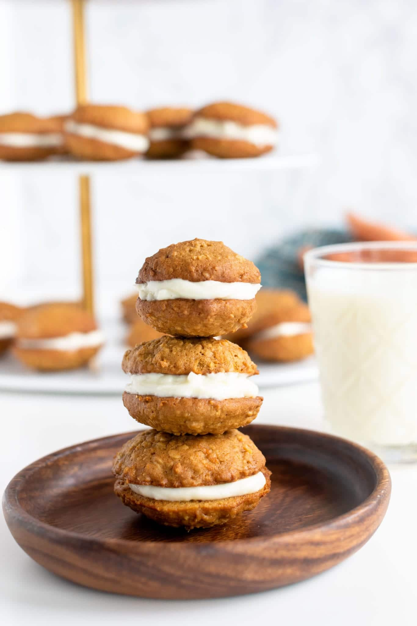 three cookie sandwiches stacked on top of each other on wooden plate served with milk with tiered display filled with cookie sandwiches in the background
