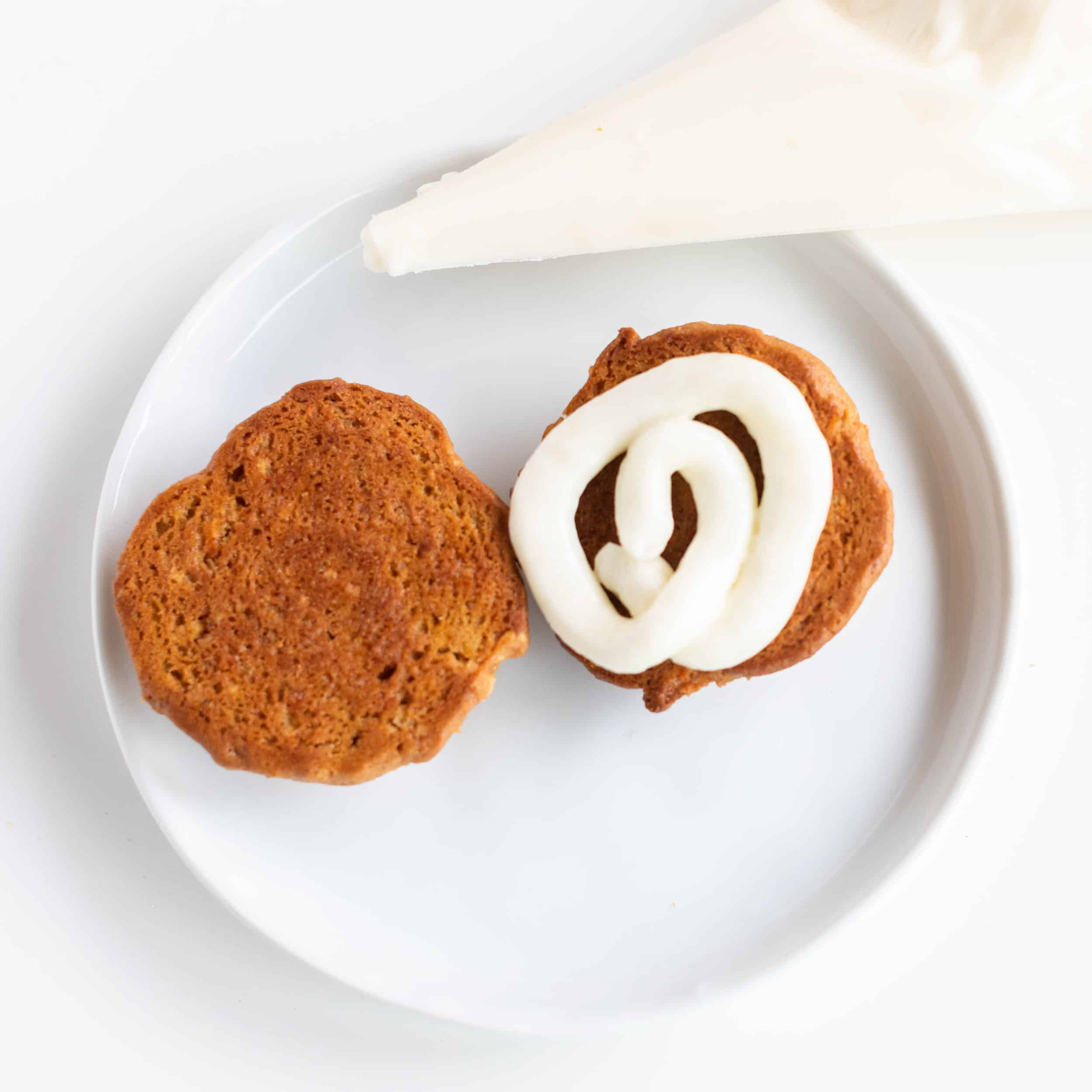 Two cookies with cream cheese frosting piped in the middle to sandwich them on white plate