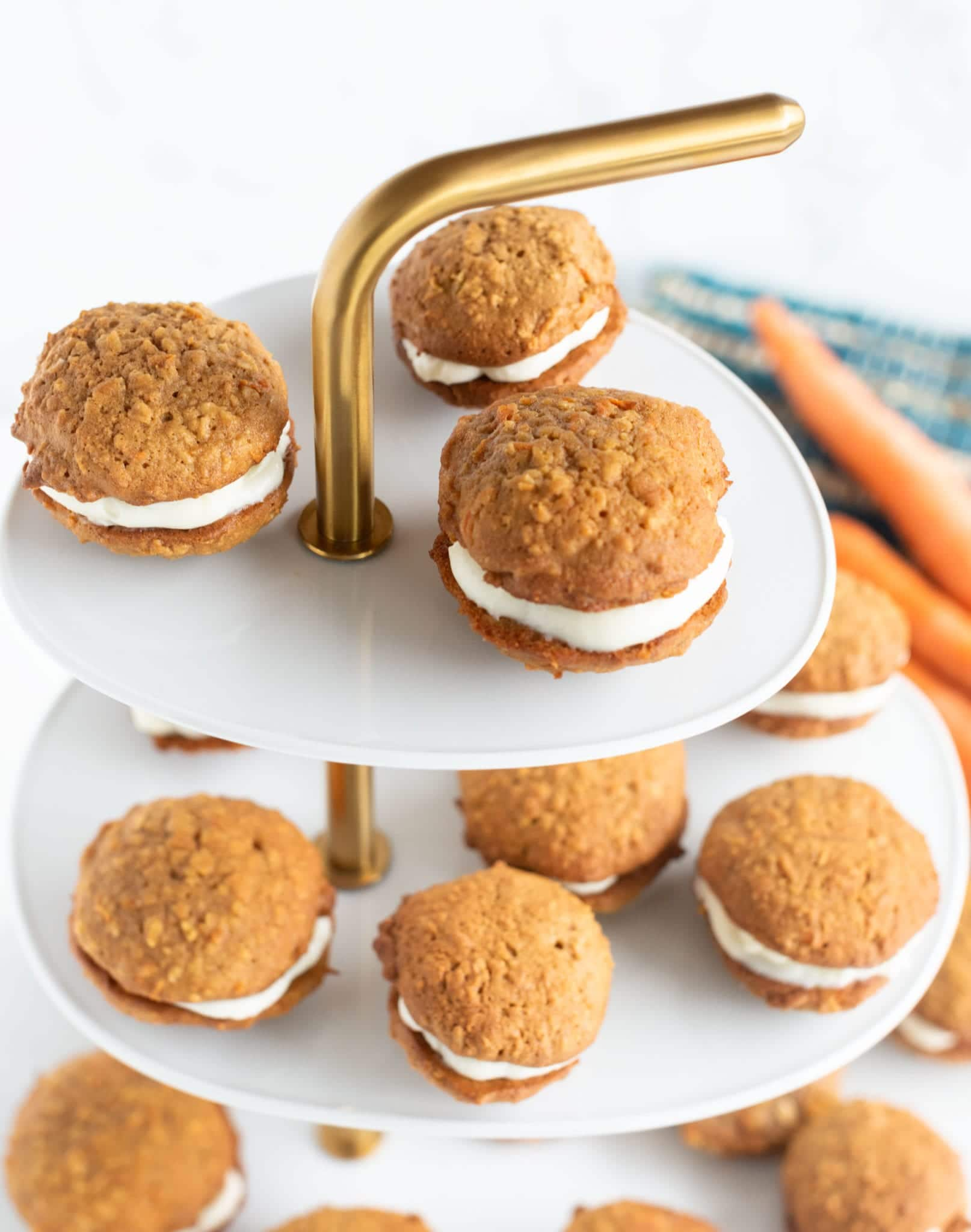 Up close shot of finished cookie sandwiches on white and gold tiered display