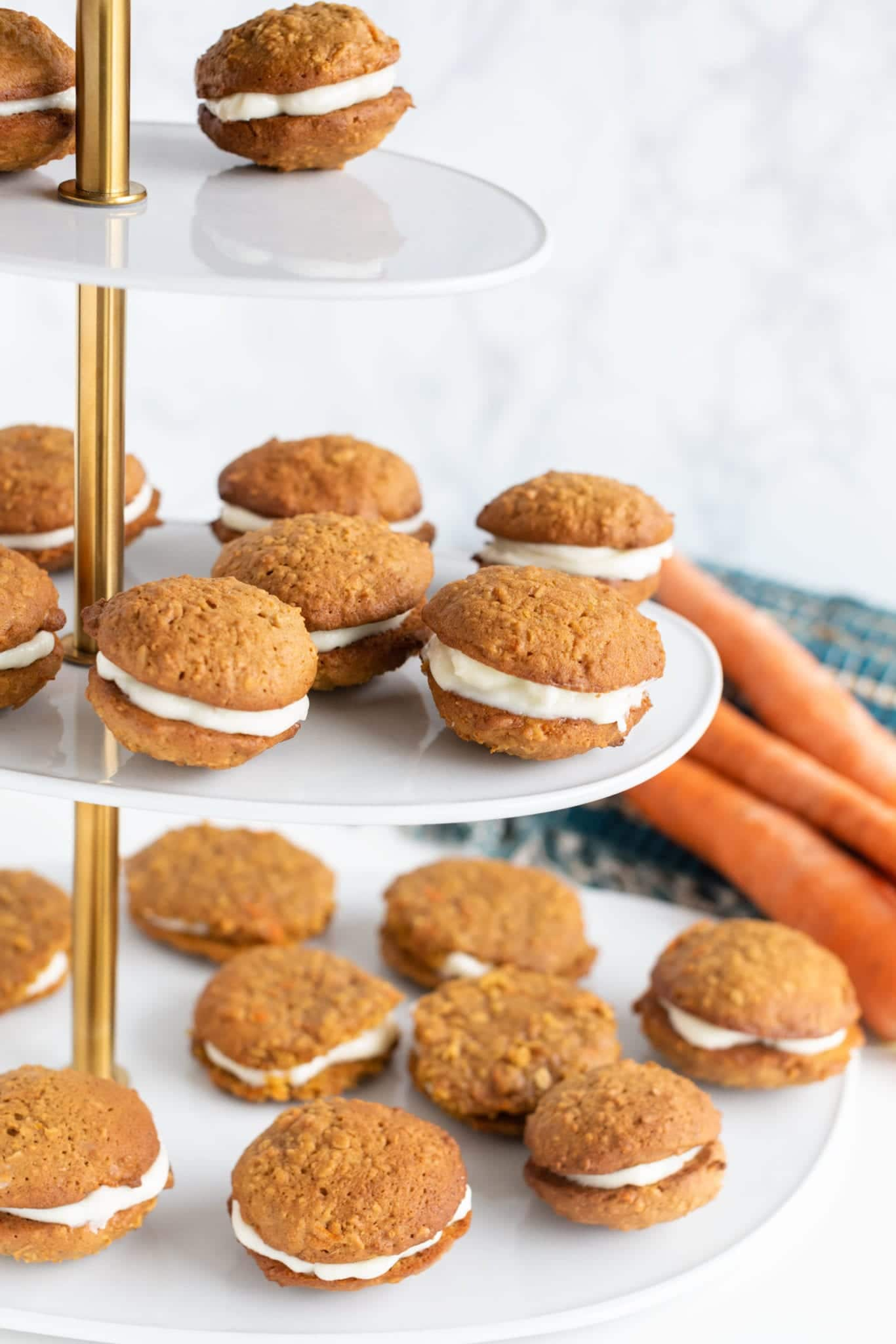 finished frosted carrot cookie sandwiches on tiered white and gold display ready to serve!