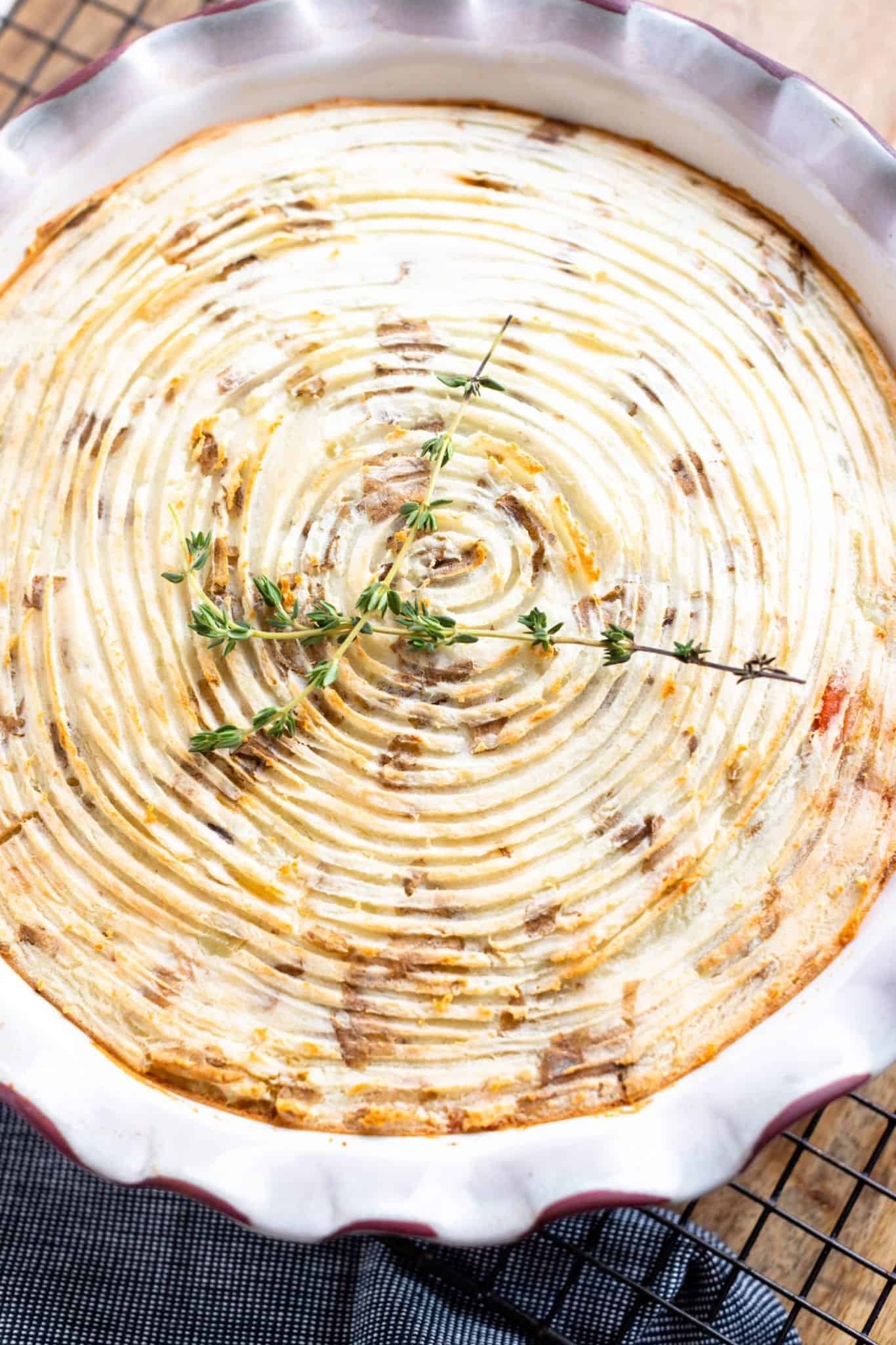shepherd's pie with golden mashed potatoes and fresh thyme in pie dish on a butchers block with cooling rack and denim napkin. #shepherdspie #weightwatchers #ww #groundturkeyrecipe #irishrecipes #dinnerrecipes #cottagepie