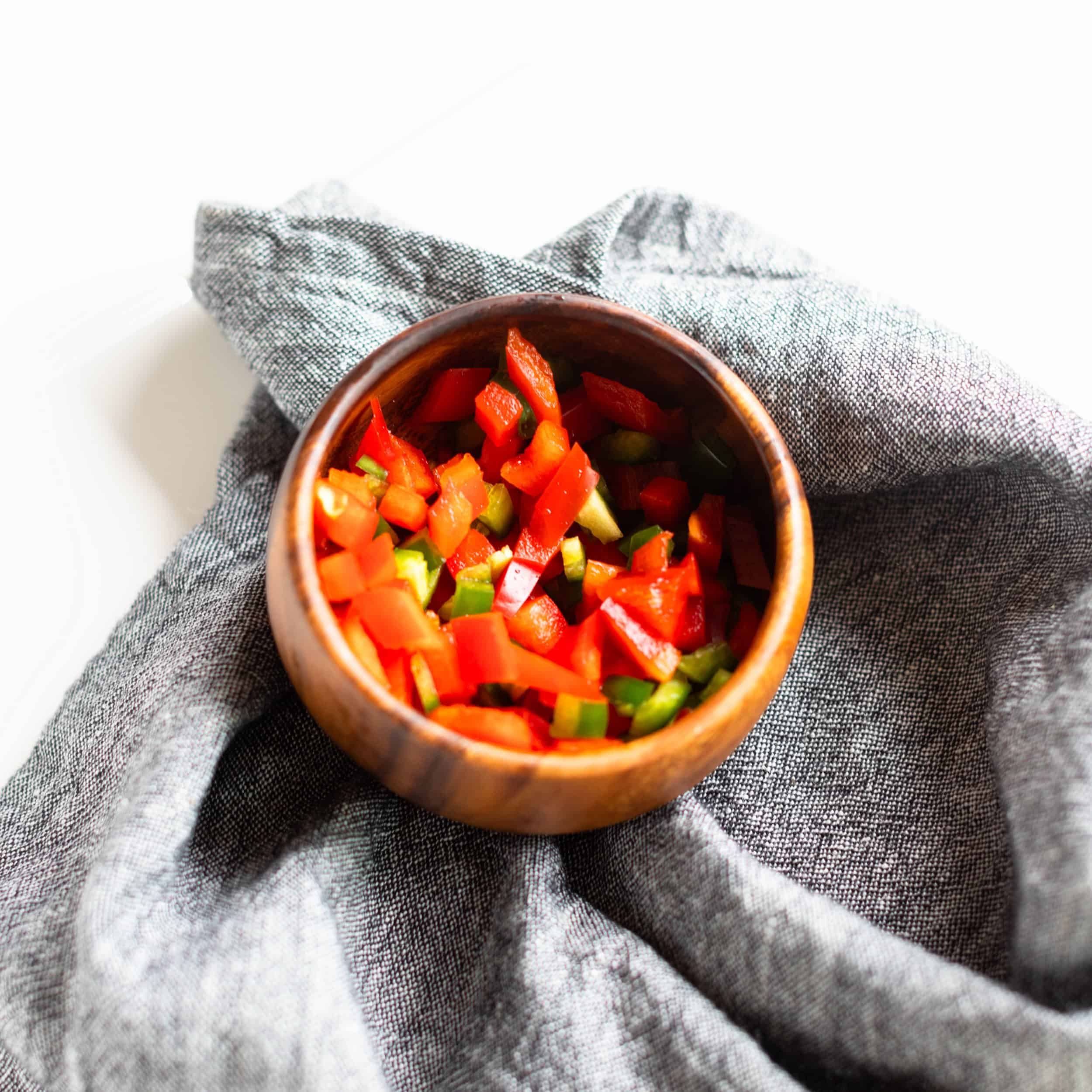 wood bowl on denim napkin holding additional vegetable ingredients for fried rice: red pepper and jalapeño