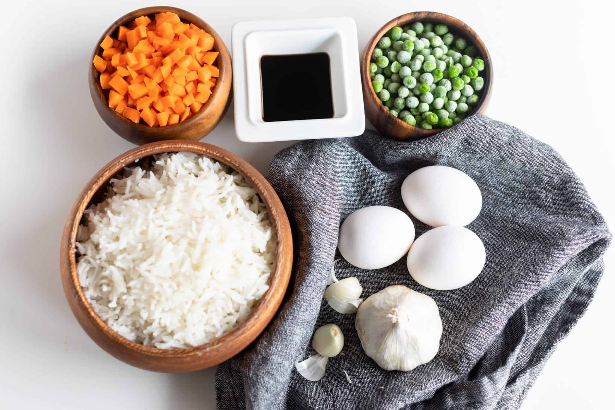 picture of prepped ingredients of make fried rice. Diced carrots, reduced sodium soy sauce, peas, cooked rice, eggs and garlic.