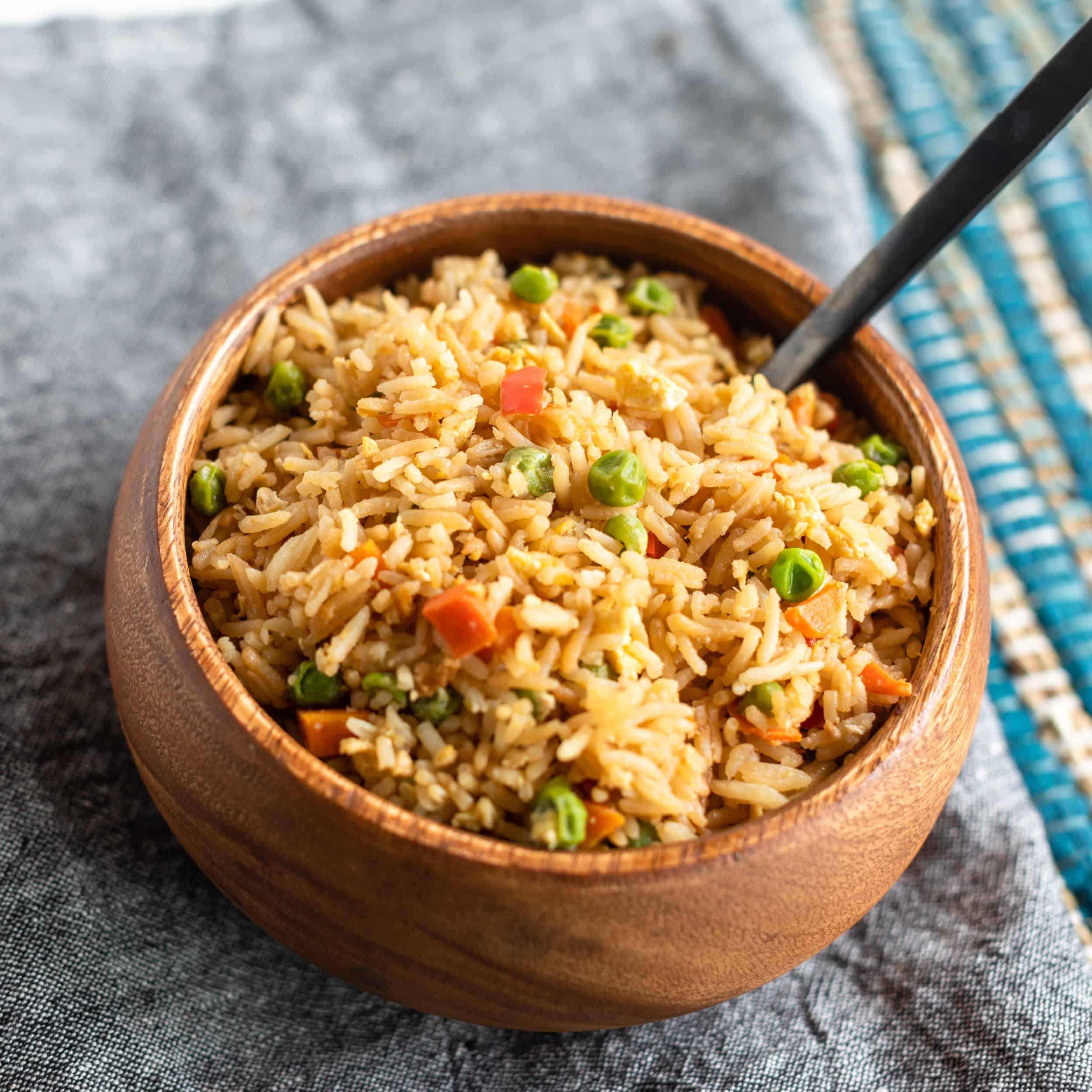 Up close picture of finished fried rice ready to serve in a wooden bowl on denim napkin and serving spoon