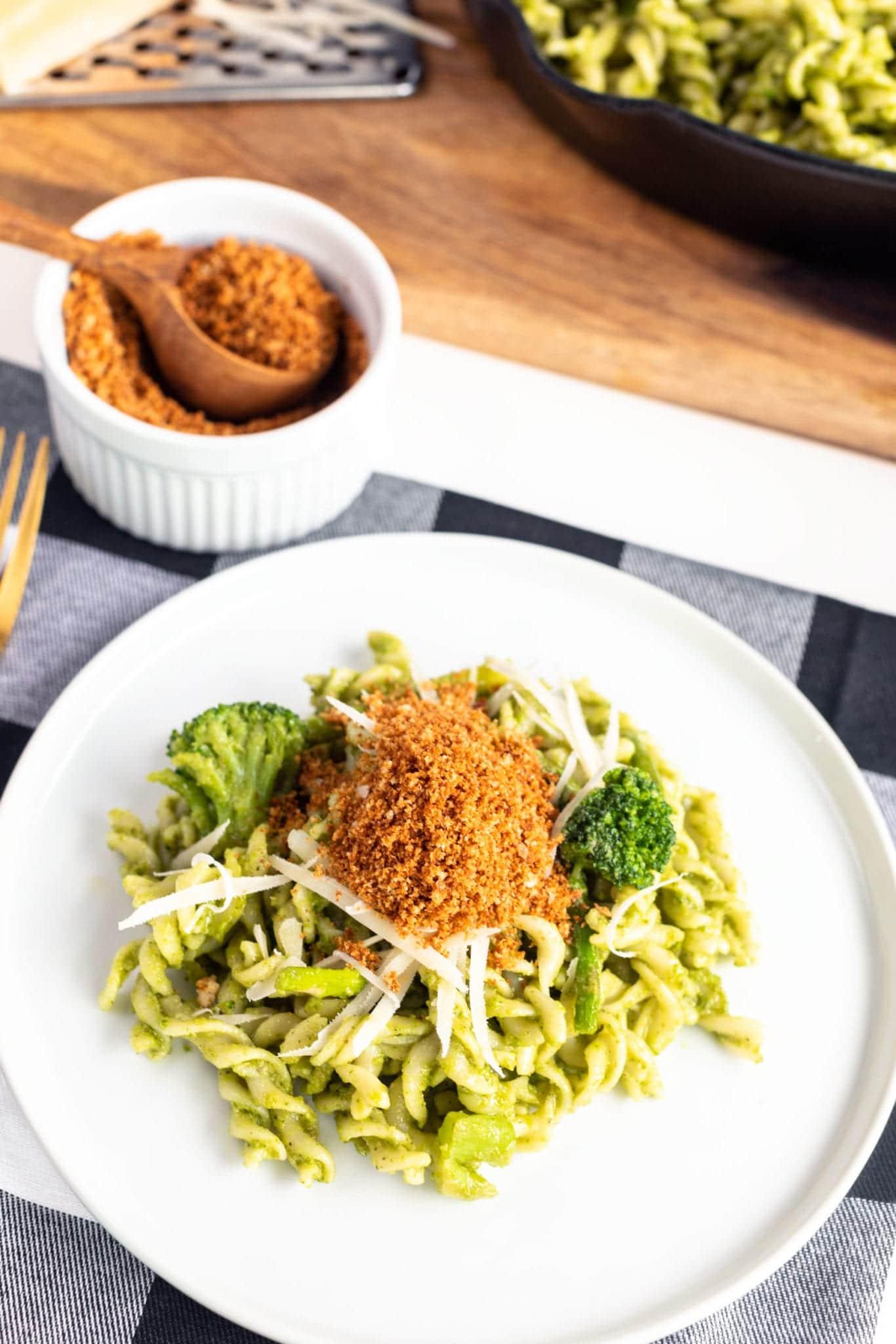 Fusilli Pasta & Fresh Basil Pesto with Toasted Breadcrumbs on white plate with plaid napkin. #pestopasta #easyrecipes #fusilli #greenrecipes #weeknightrecipes #pastadish #pasta #breadcrumbs #massimobottura