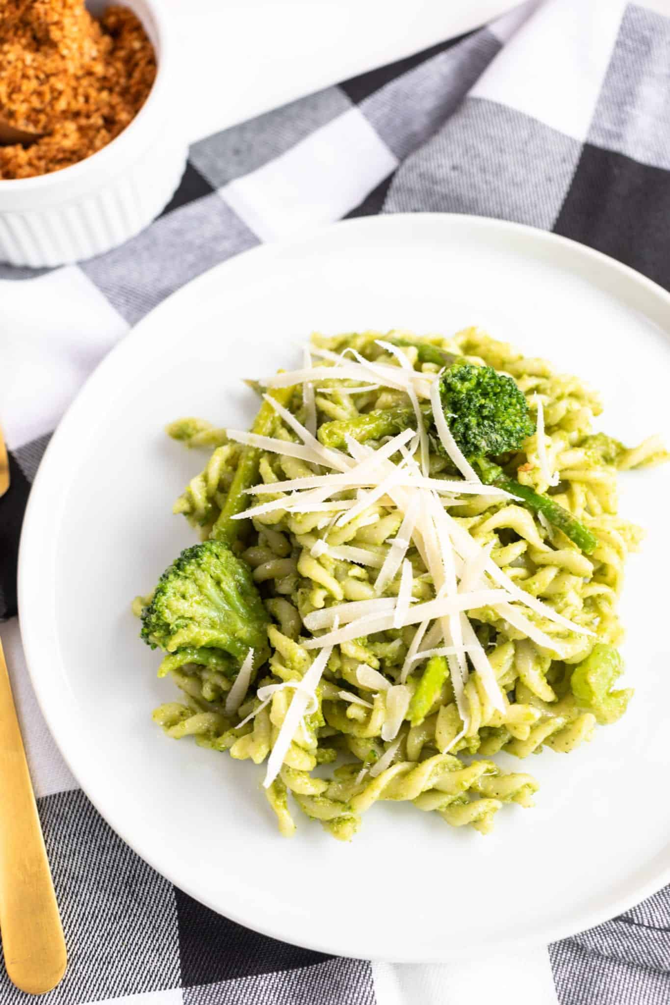 Fusilli Pasta & Fresh Basil Pesto with grated Parmesan on top. Served on white plate with plaid napkin and toasted breadcrumbs on the side served in white ramekin with wooden spoon. #pestopasta #easyrecipes #fusilli #greenrecipes #weeknightrecipes #pastadish #pasta #breadcrumbs #massimobottura