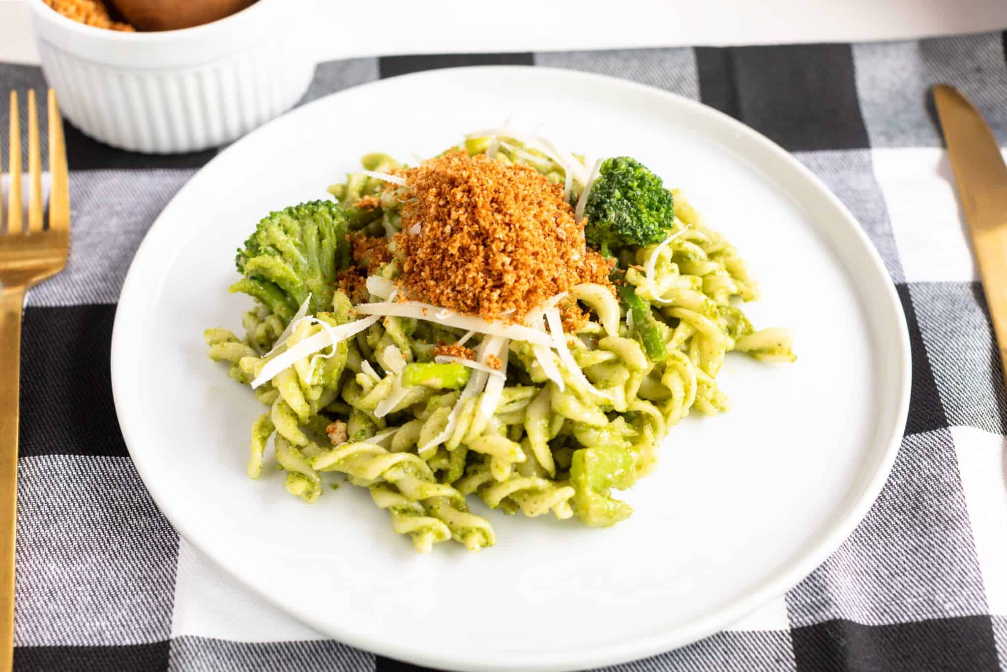 Fusilli Pasta & Fresh Basil Pesto with Toasted Breadcrumbs on white plate with plaid napkin and gold fork and knife. Additional toasted breadcrumbs served on the side. #pestopasta #easyrecipes #fusilli #greenrecipes #weeknightrecipes #pastadish #pasta #breadcrumbs #massimobottura