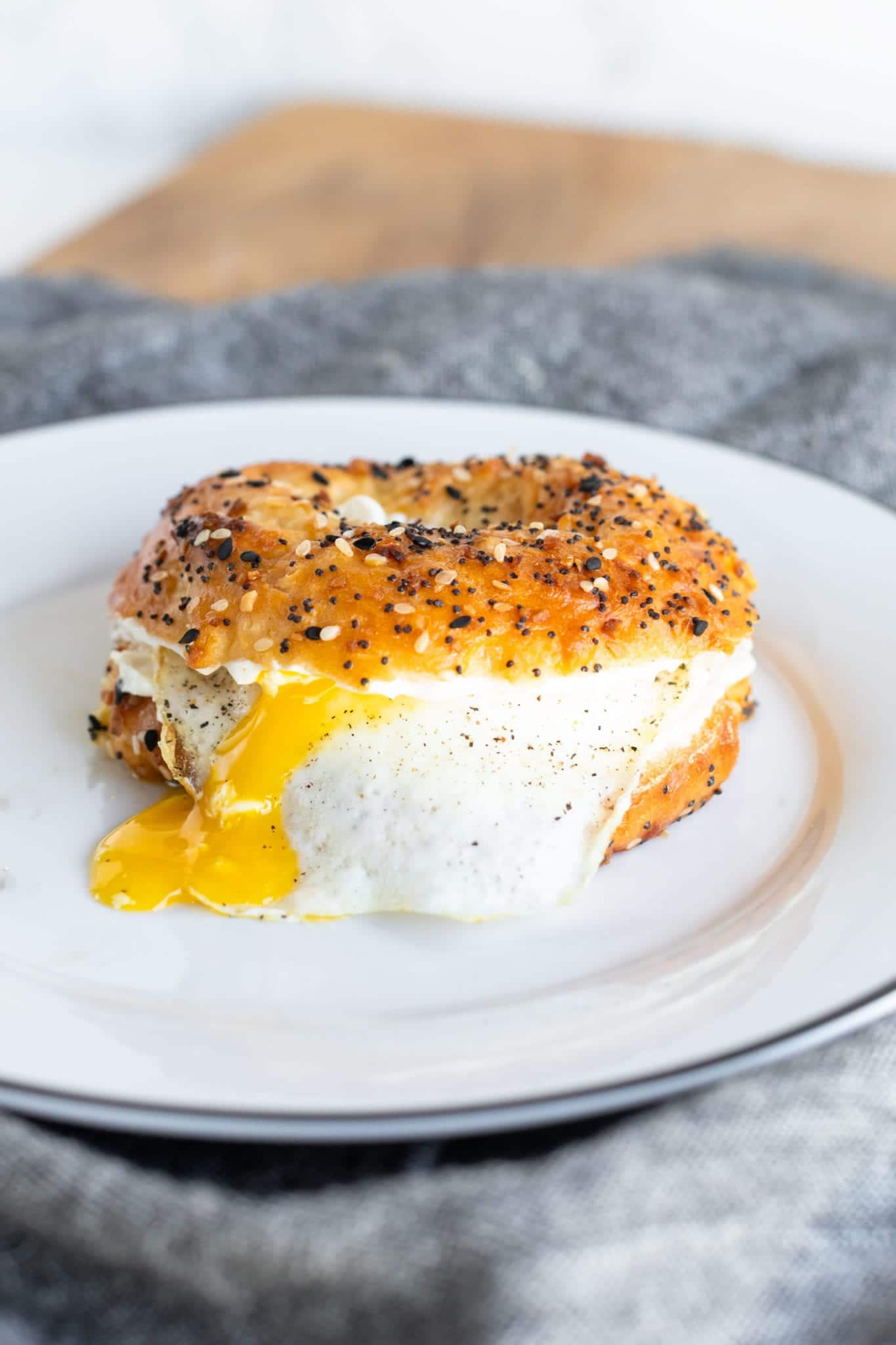 EASY Homemade Everything Bagels served as an egg and cream cheese sandwich on a white plate with denim napkin. #breakfast #easyrecipes #homemadebagels #everythingbagels #weightwatchers