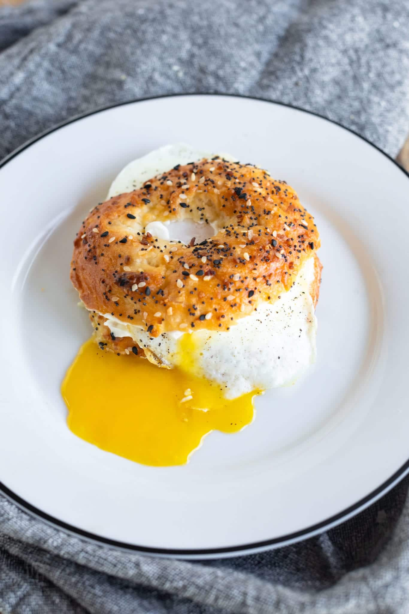 EASY Homemade Everything Bagels with cream cheese and over easy egg with runny yolk dripping down the side ready to eat! #breakfast #easyrecipes #homemadebagels #everythingbagels #weightwatchers
