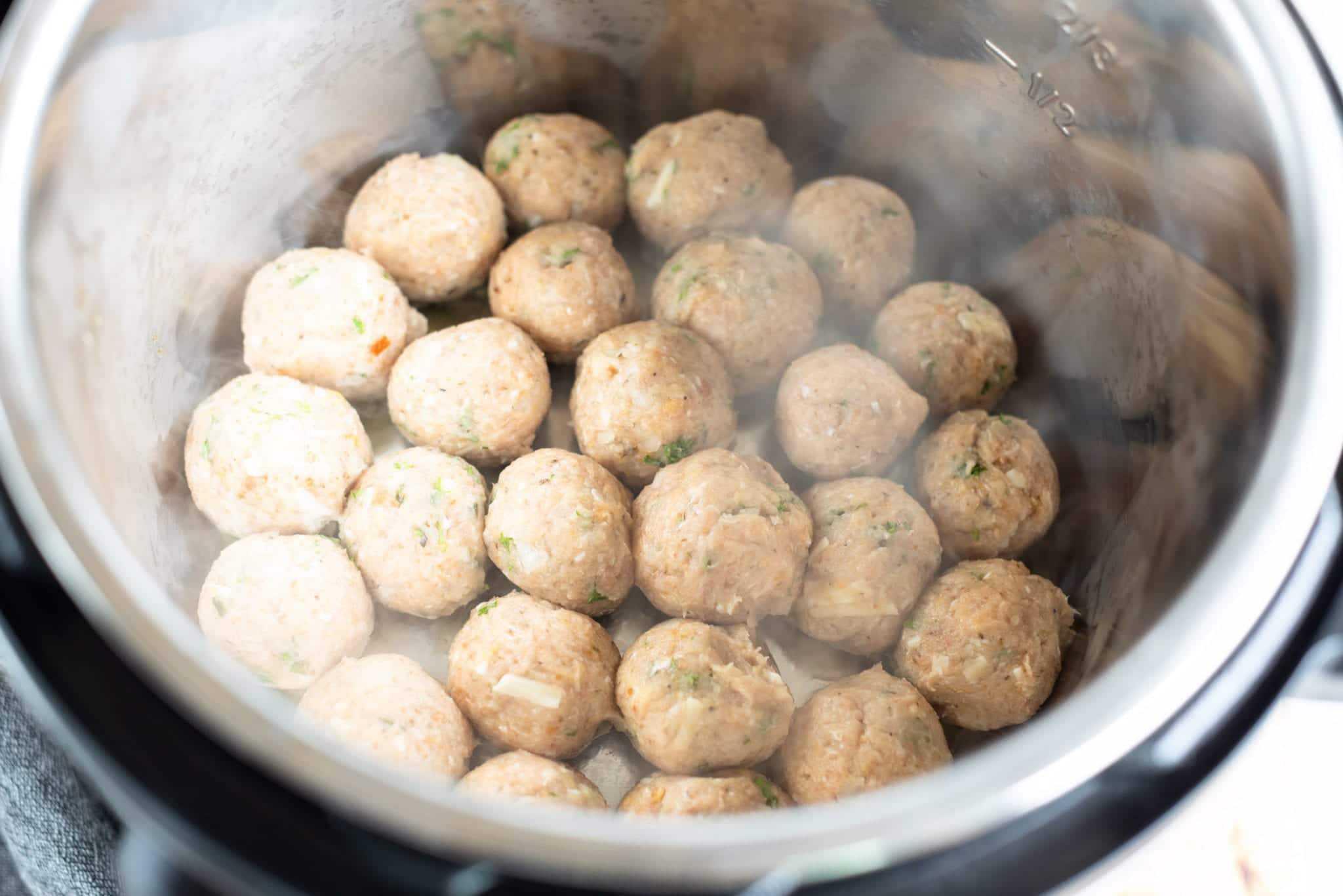 overhead shot sautéing greek turkey meatballs in instant pot with oil