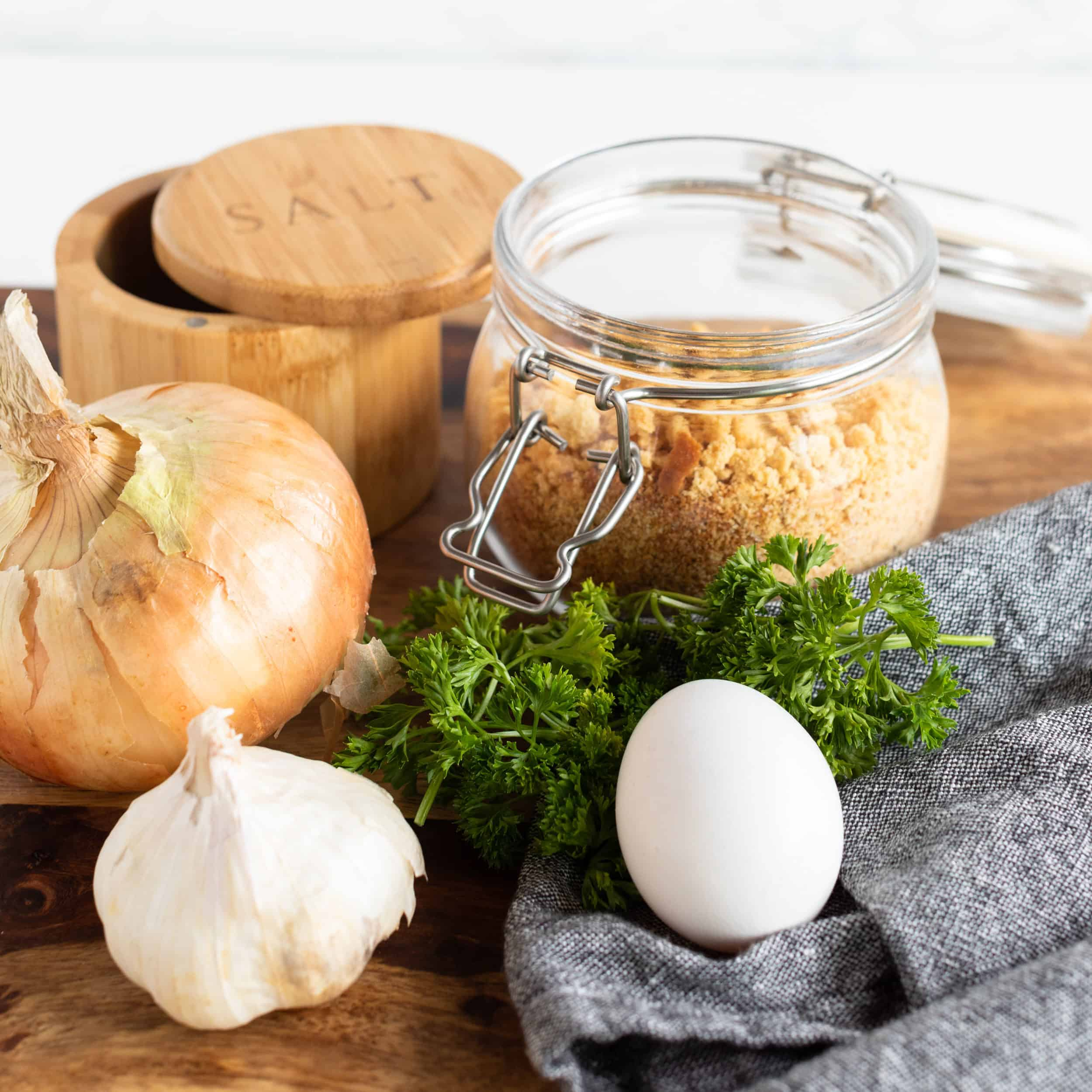 ingredient picture of egg, parsley, onion, garlic, sea salt flakes, and bread crumbs