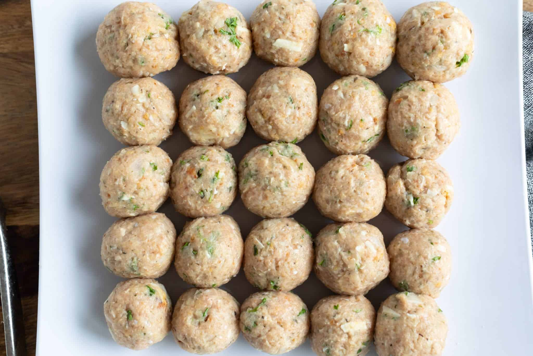 overhead shot of 25 Greek Turkey Meatballs rolled and prepped on white plate ready to cook