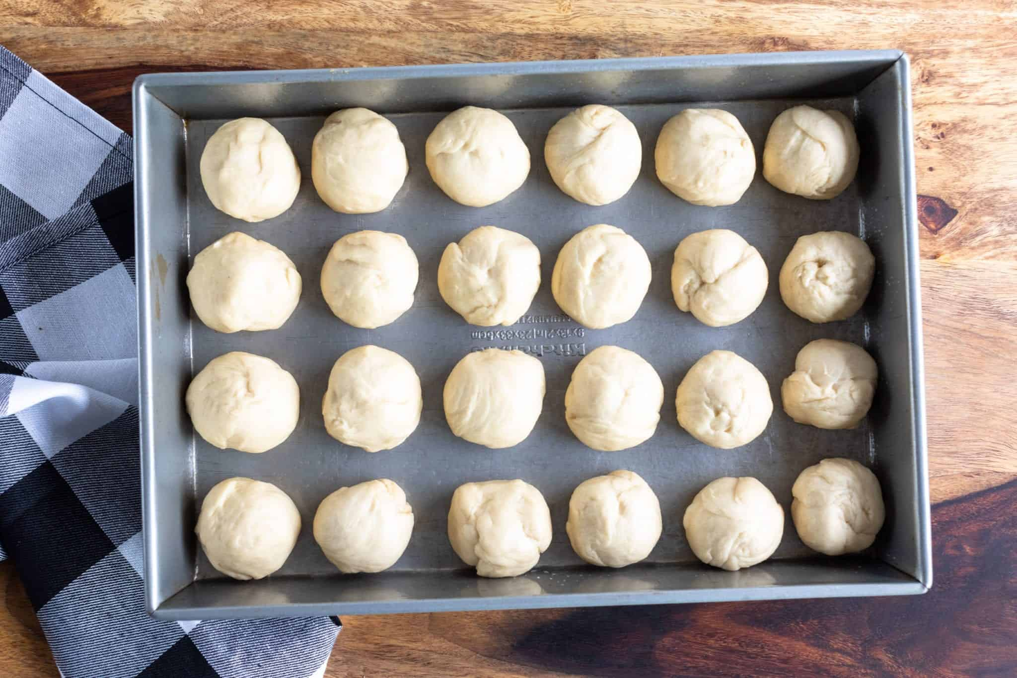 Hawaiian sweet roll dough evenly portioned into 24 rolls in 9 x 13 bakeware dish ready before rising and proofing.