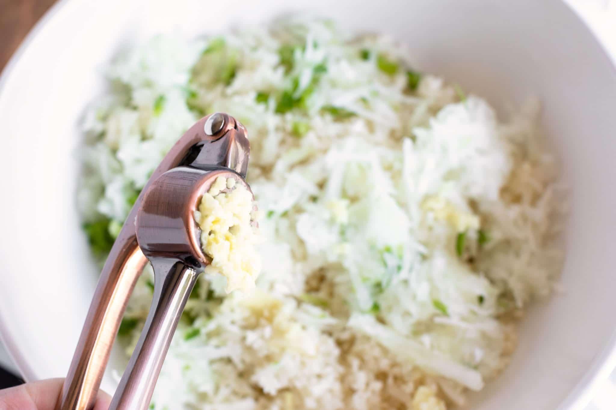 Zulay Kitchen Garlic press, pressing garlic clove for crispy cauliflower hashbrown recipe