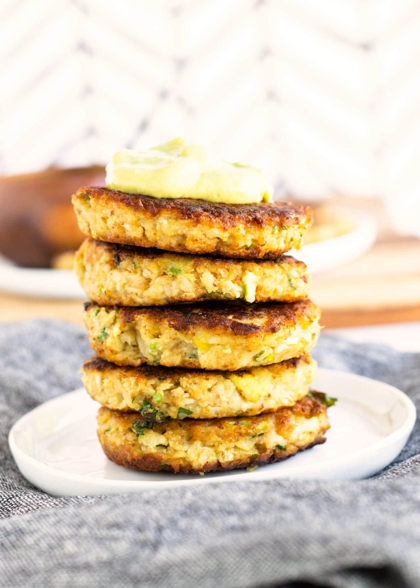 Crispy Cauliflower Hash Browns stacked and served on white plate with creamy avocado dip on top